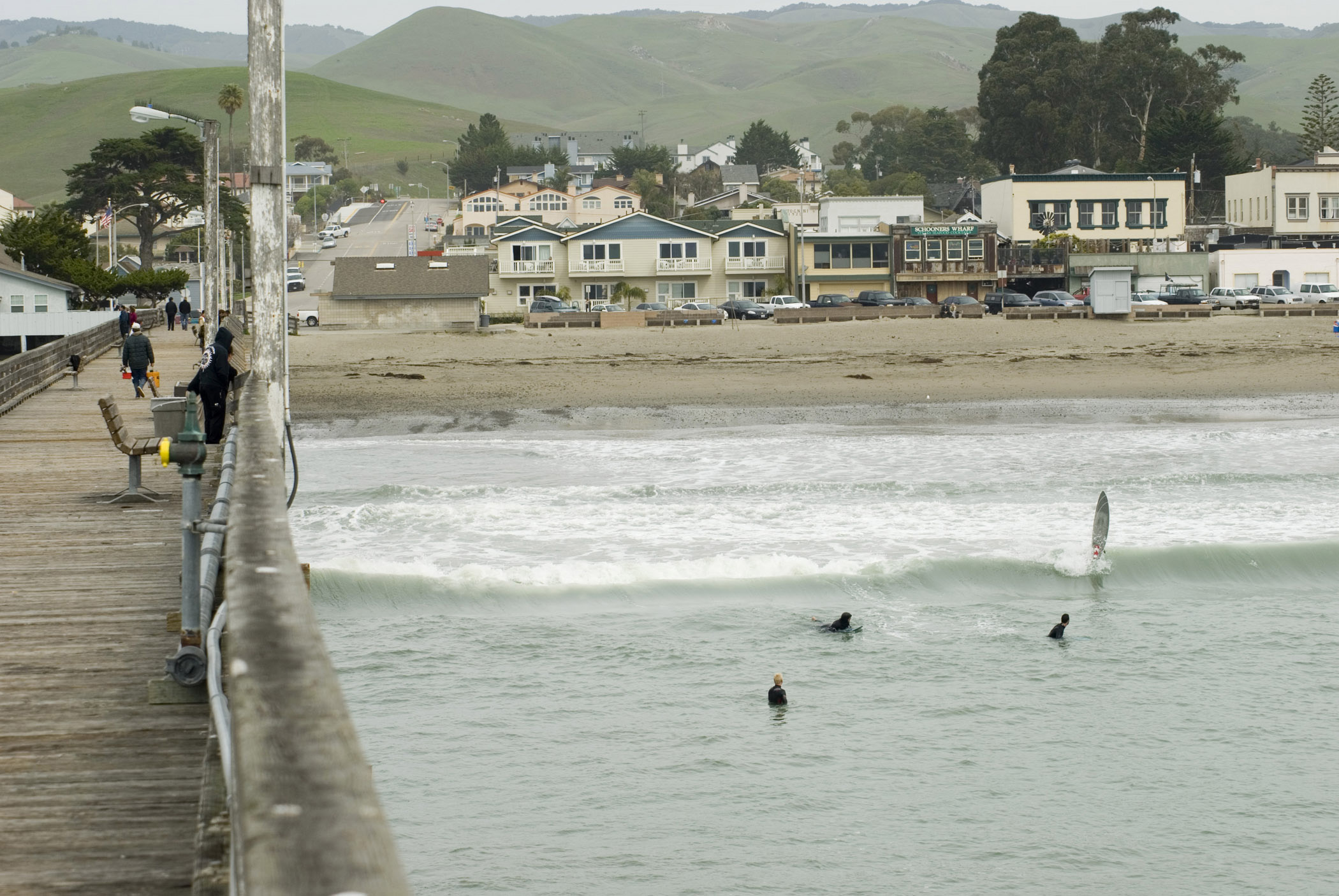 View along the wooden jetty or pier in Cayucos State Beach Park looking towards the beach with surfers in the water below