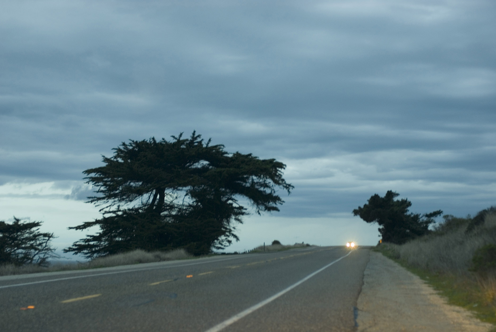 Low angle view with an approaching car with headlights illuminated on Highway 1 on the Big Sur Coast, California