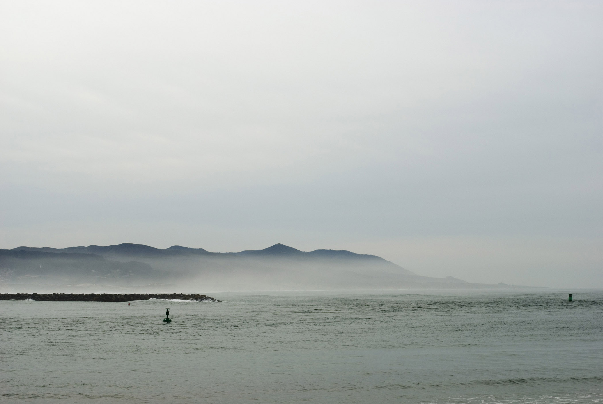 Morro Bay coastline in California with a calm flat ocean and light sea mist