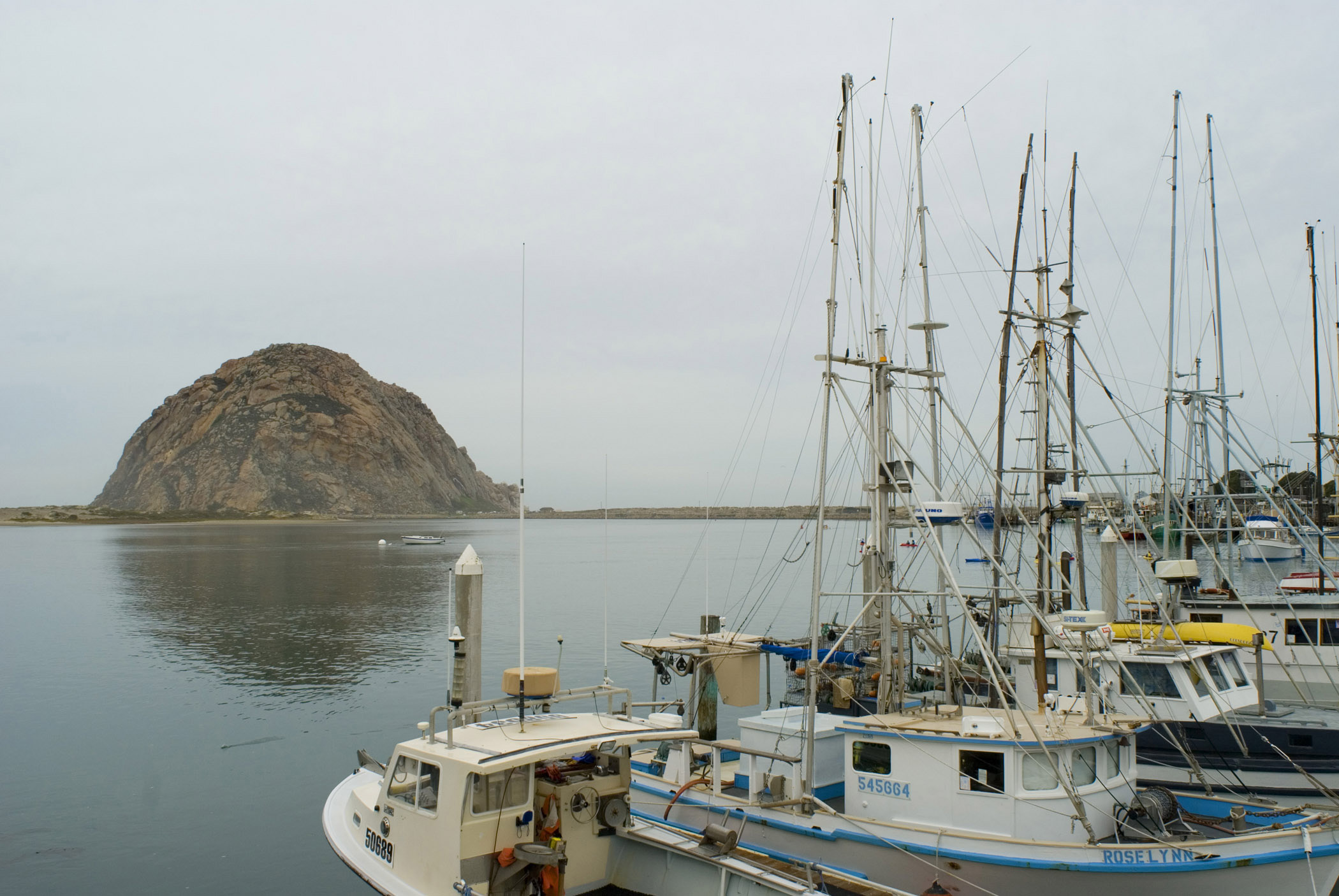 Boats at Morro Bay Dock and Famous Morro Rock Afar. Against an overcast grey sky background.