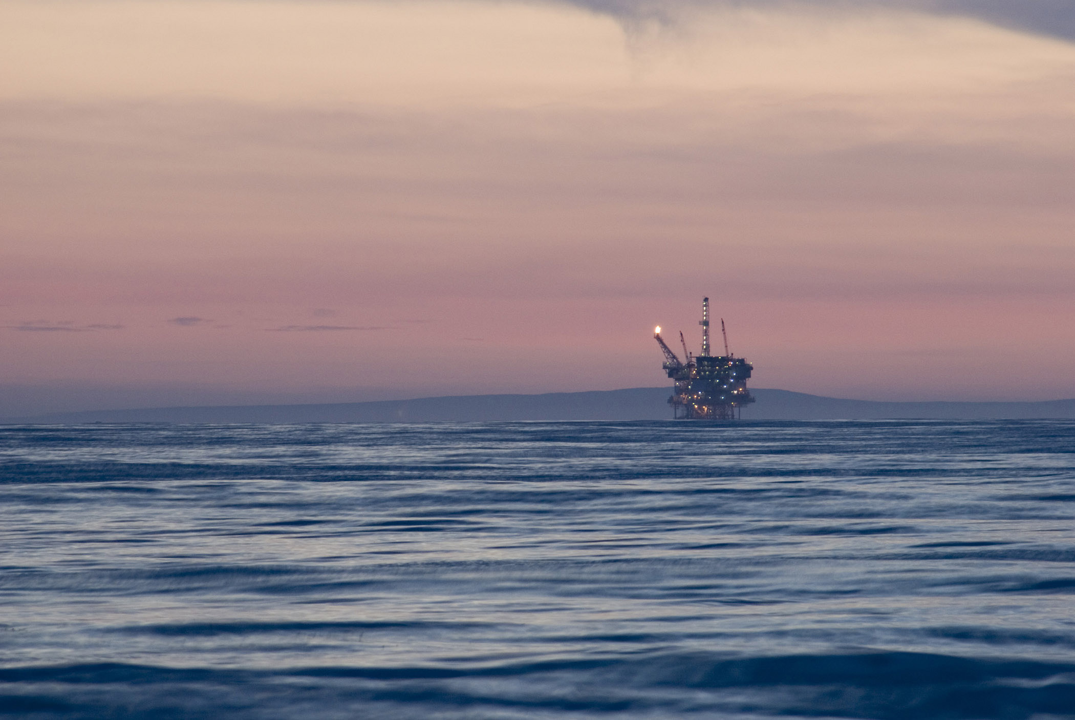 Offshore oil rig in the Gulf of Mexico off California at dusk with a colorful pink sky above a calm ocean