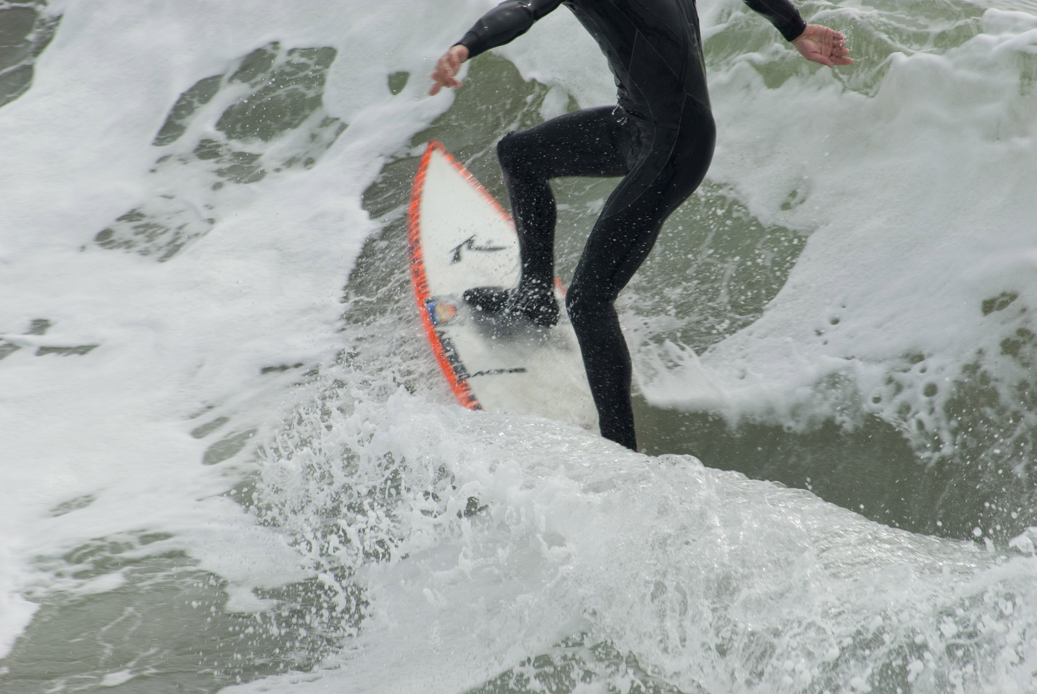 California surfer showing the legs of a person in a wetsuit balancing on a surfboard in a breaking wave with white surf