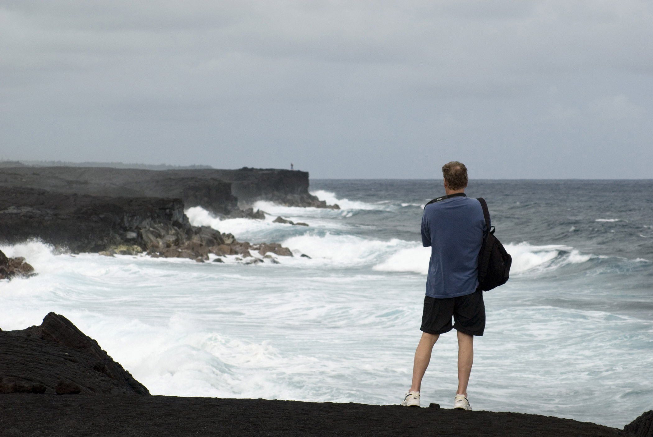 Tourist standing with his back to the camera on the black volcanic sand on Kalapana beach, Hawaii looking out over the ocean waves and rocks