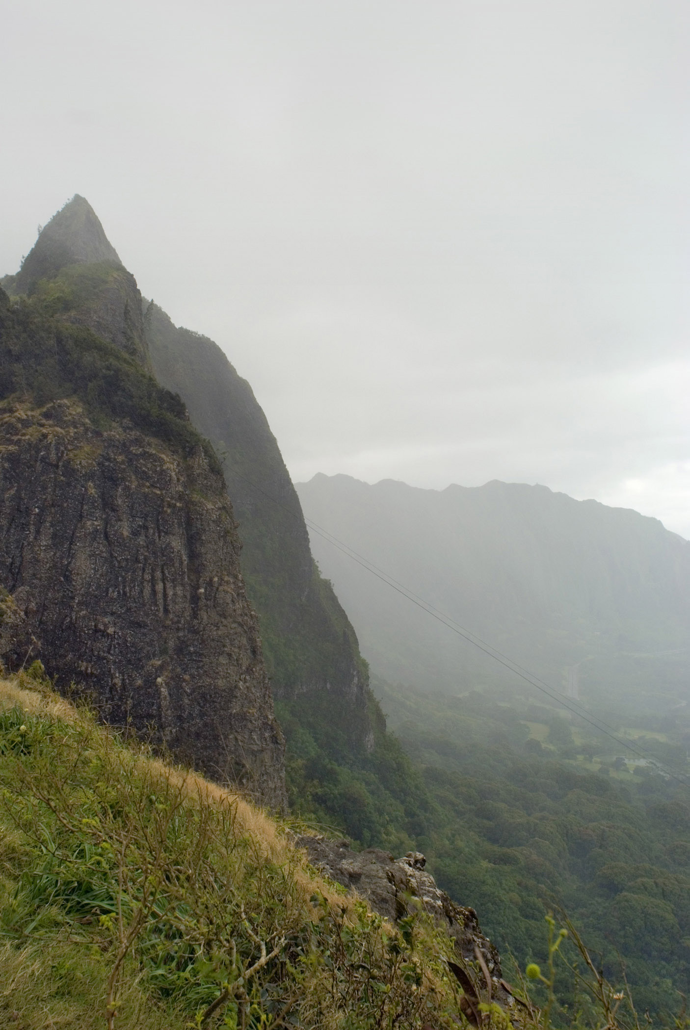 View from the Pali Lookout in Ohau, Hawaaii looking out over the mountain ranges on a rainy misty atmospheric day
