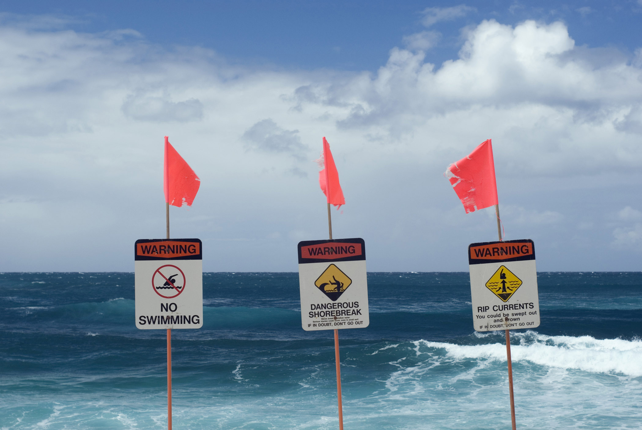 Three No Swimming Warning Signage with Small Flags at the Blue Water Beach.