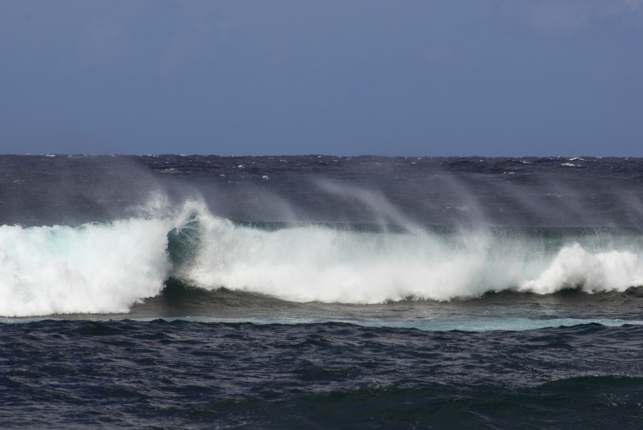 Big waves off the North Shore, Hawaii with spray whipped up by the wind, a popular area for surfers