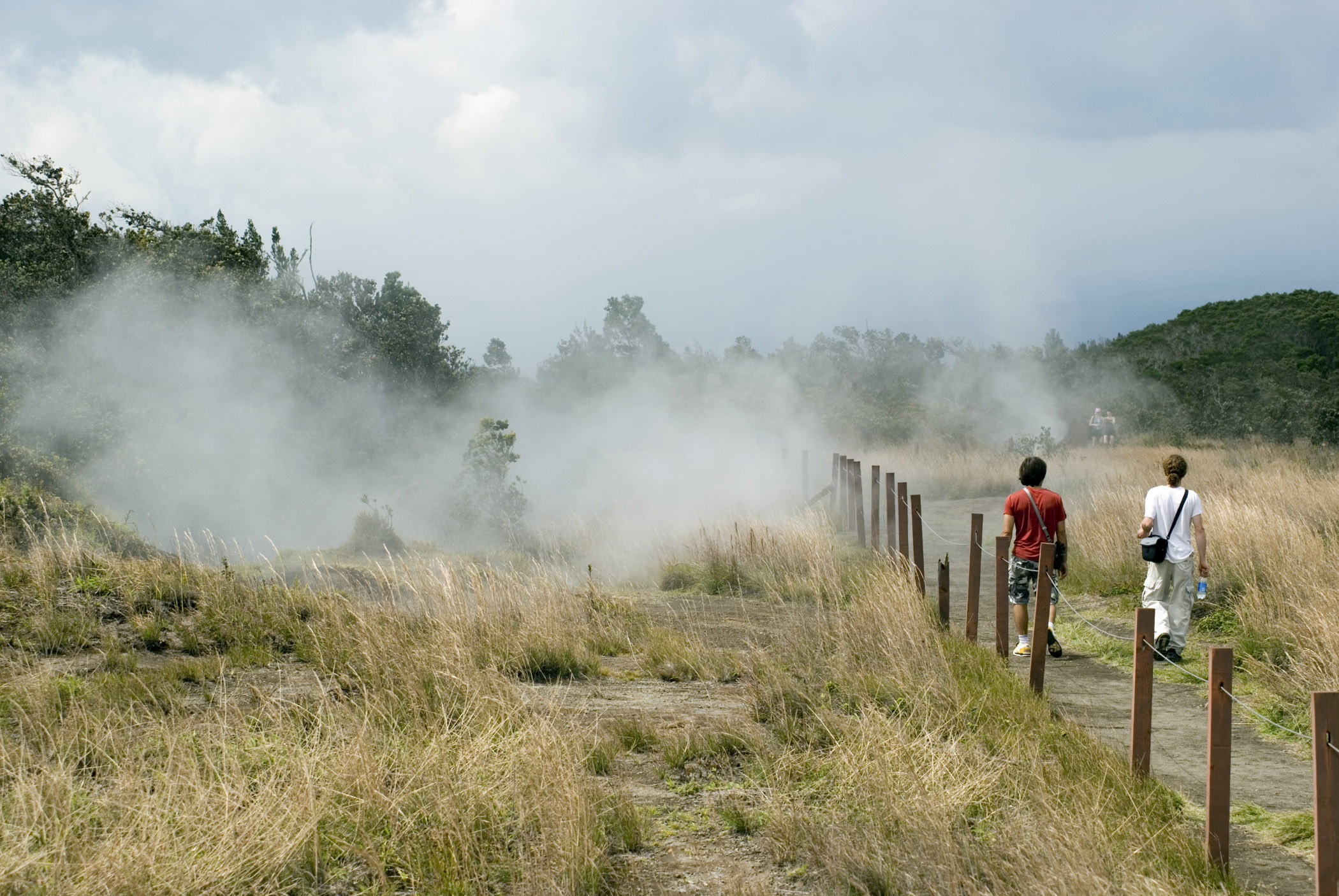 Tourists taking the crater walk in the Volcanoes National Park on Hawaii passing volcanic steam vents
