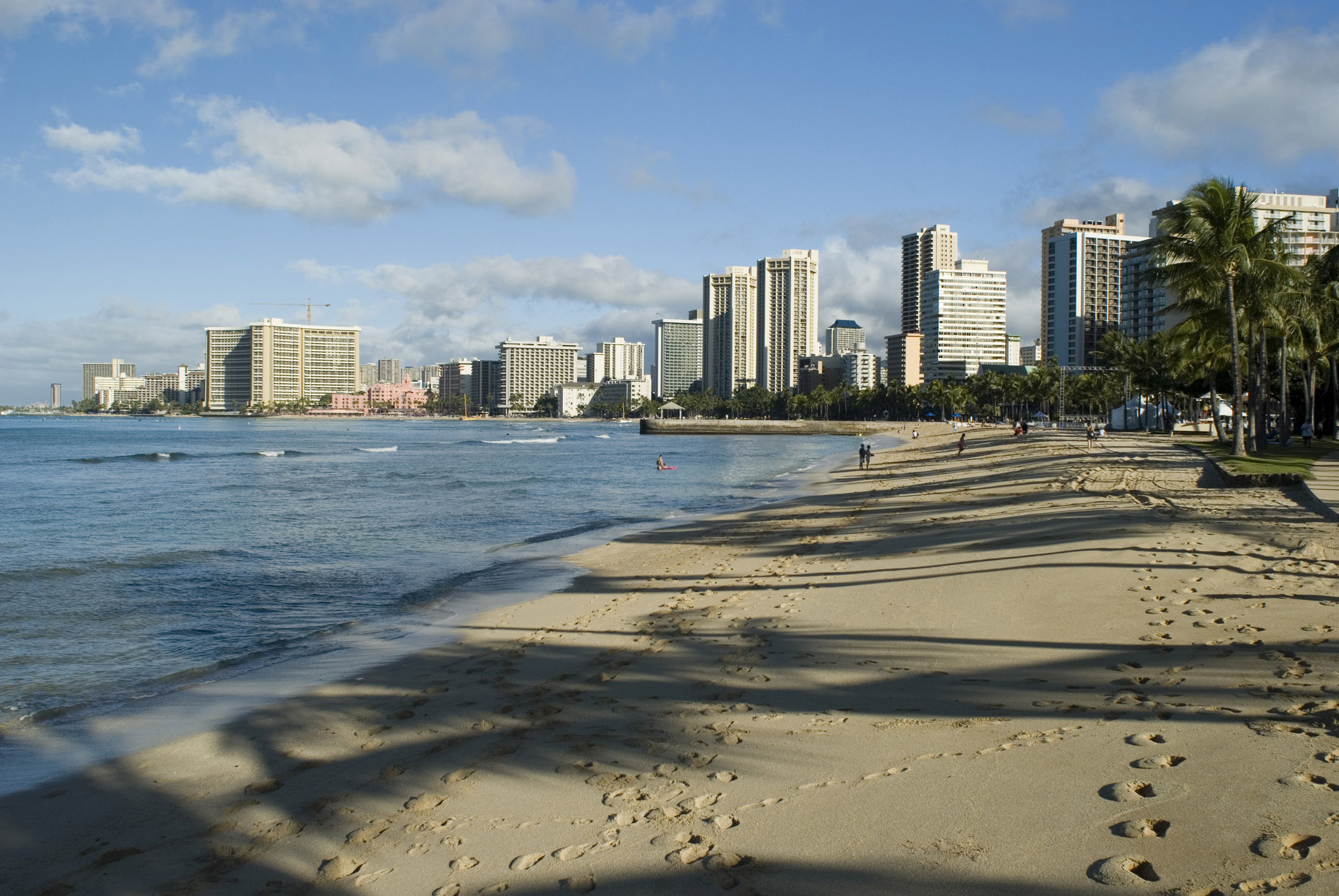 Scenic view of the waterfront and city skyline with footsteps across the golden sand of Waikiki beach, Honolulu, Hawaii