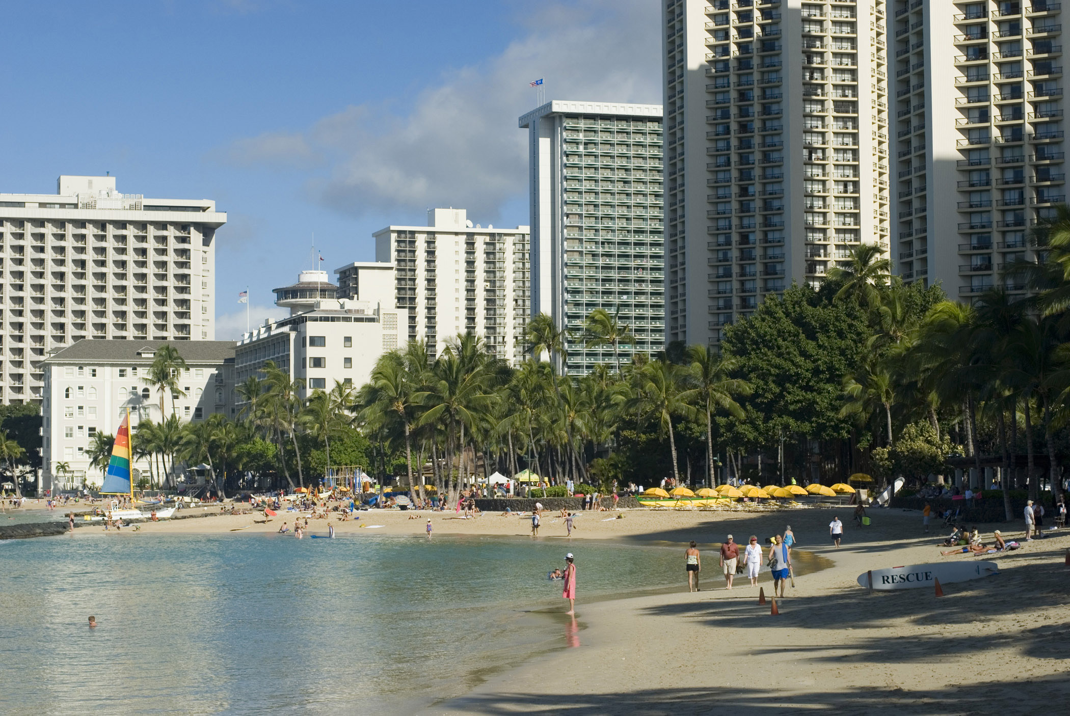 Random Tourists at Beautiful Seashore of Waikiki Beach. Captured with Huge Buildings at Beachfront.
