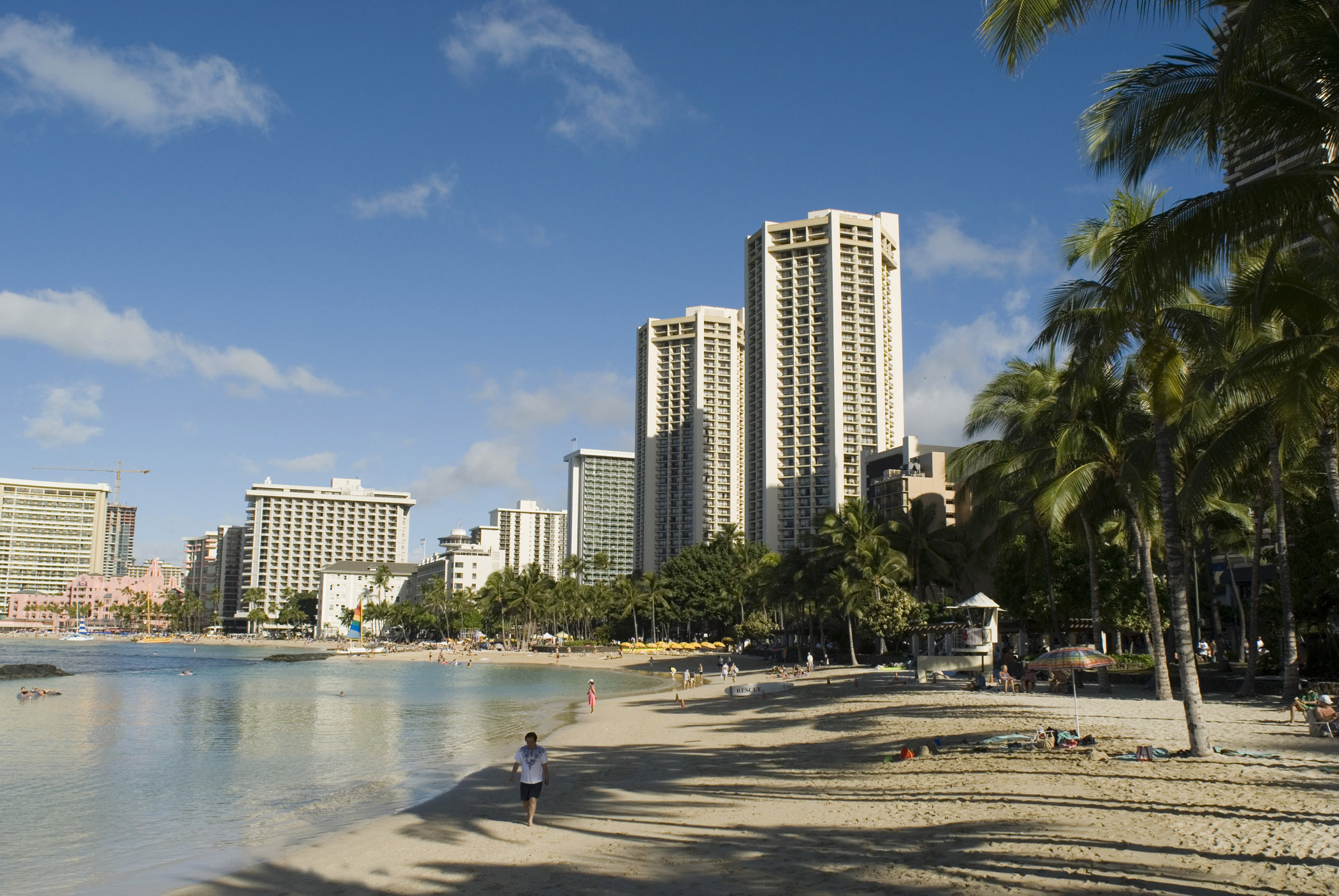 Scenic view of Waikiki Beach, Hawaii with its golden sand, palm trees and high-rise apartment blocks overlooking the bay