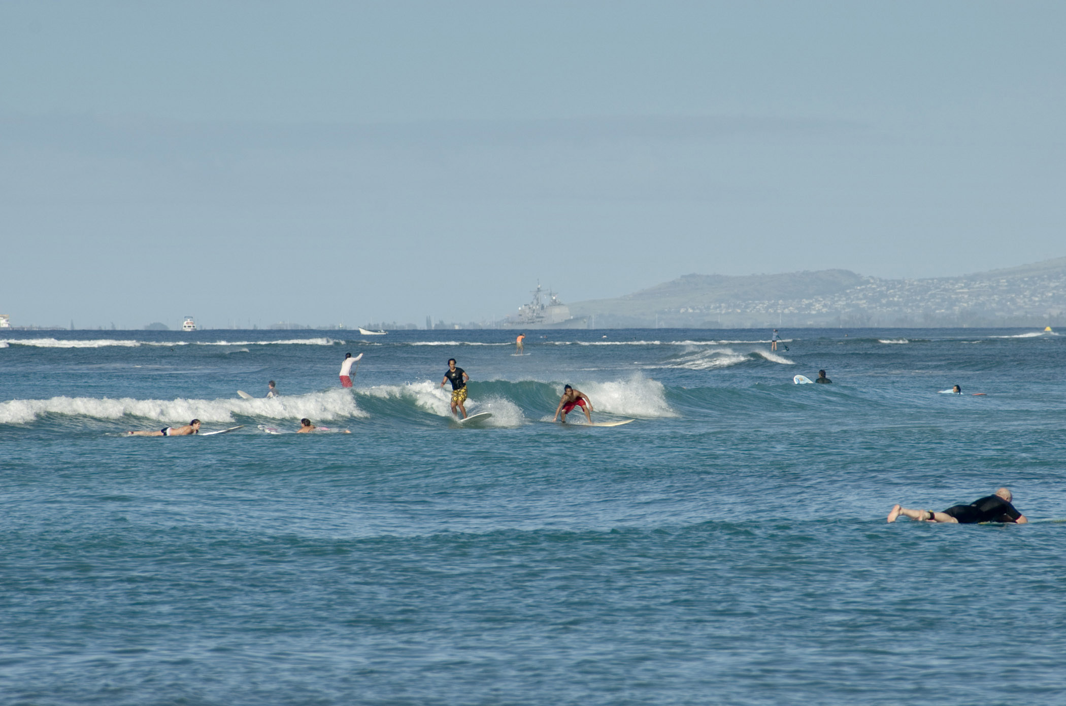 Few Tourists Surfing at Blue Water Waikiki Beach. Isolated Light Blue Gray Sky Background.