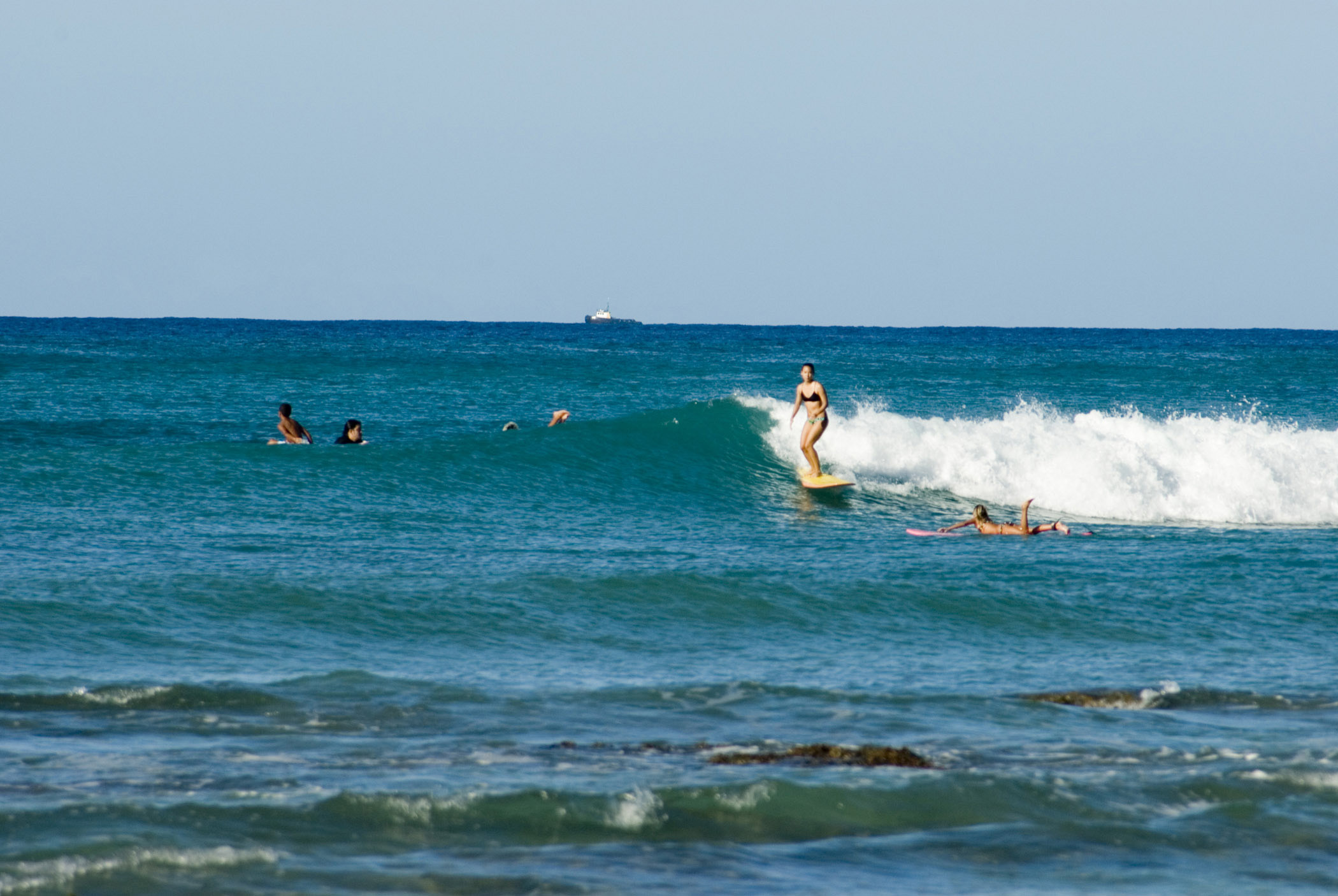 Woman surfing on Waikiki Beach riding in on a wave with other surfers paddling around her, Oahu Island, Hawaii, USA