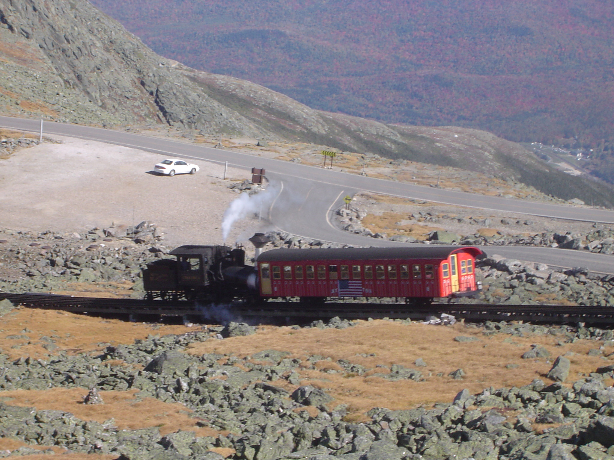 Mount Washington Cog Railway steam train negotiating a steep incline above a parking lot, USA