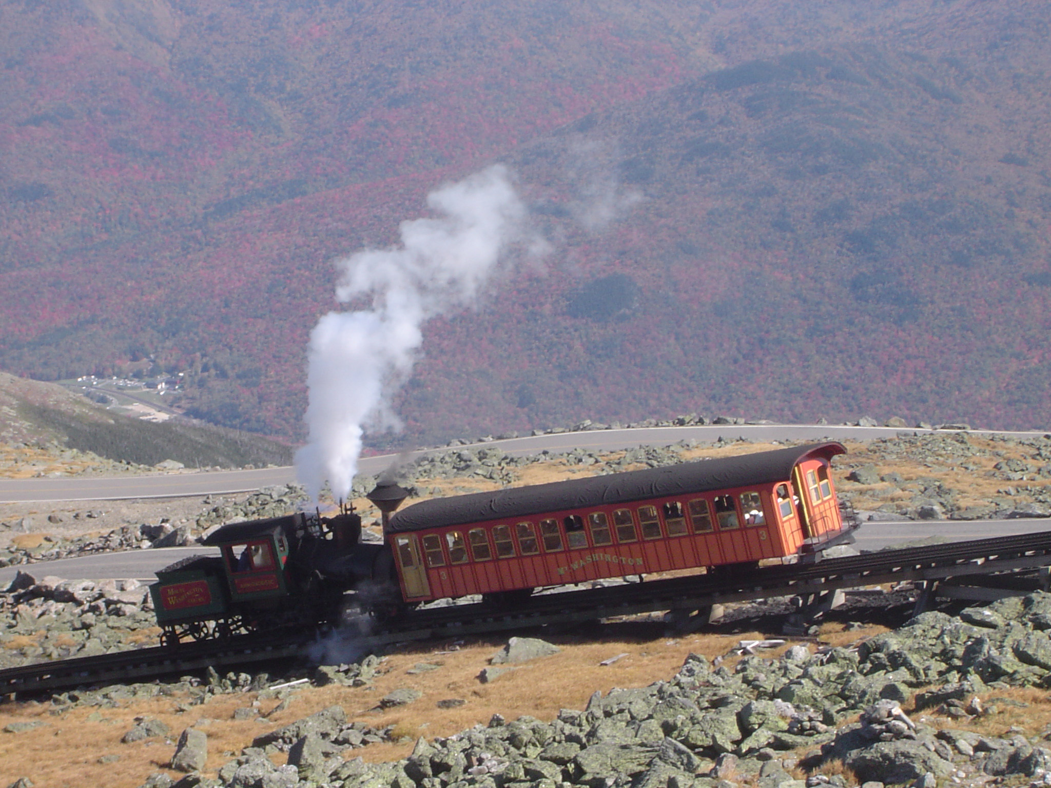 Vintage Steam Locomotive Passing Cog Railway on Rocky Landscape. Captured with Mountains Background.
