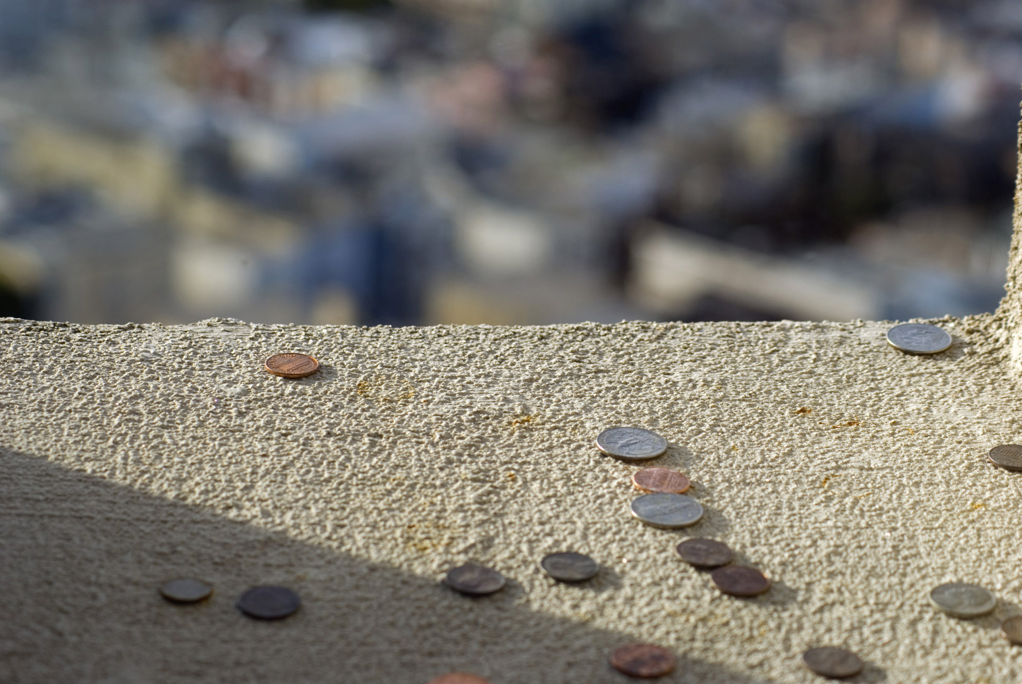 Close up Assorted Coins at Coit Concrete Tower Window in San Francisco.
