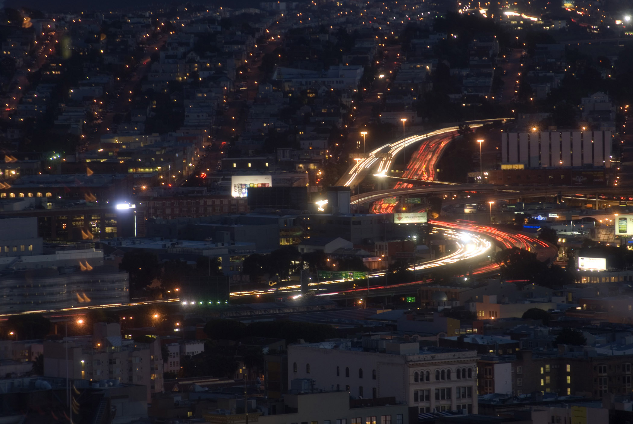 Long exposure of moving traffic on a freeway at night curving through a town lighting up the darkness