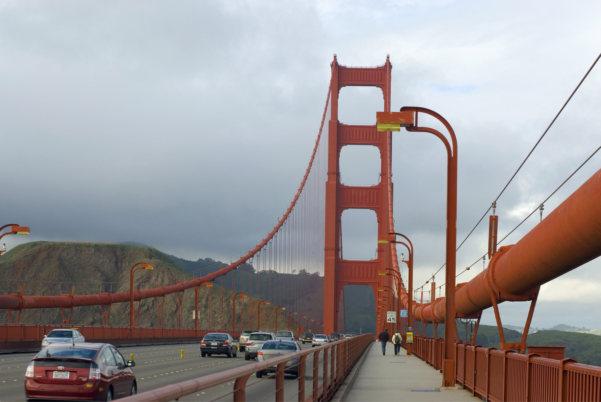 Walk Along the Golden Gate Bridge San Francisco. Captured with Mountains in the distance with a Stormy Sky Background.