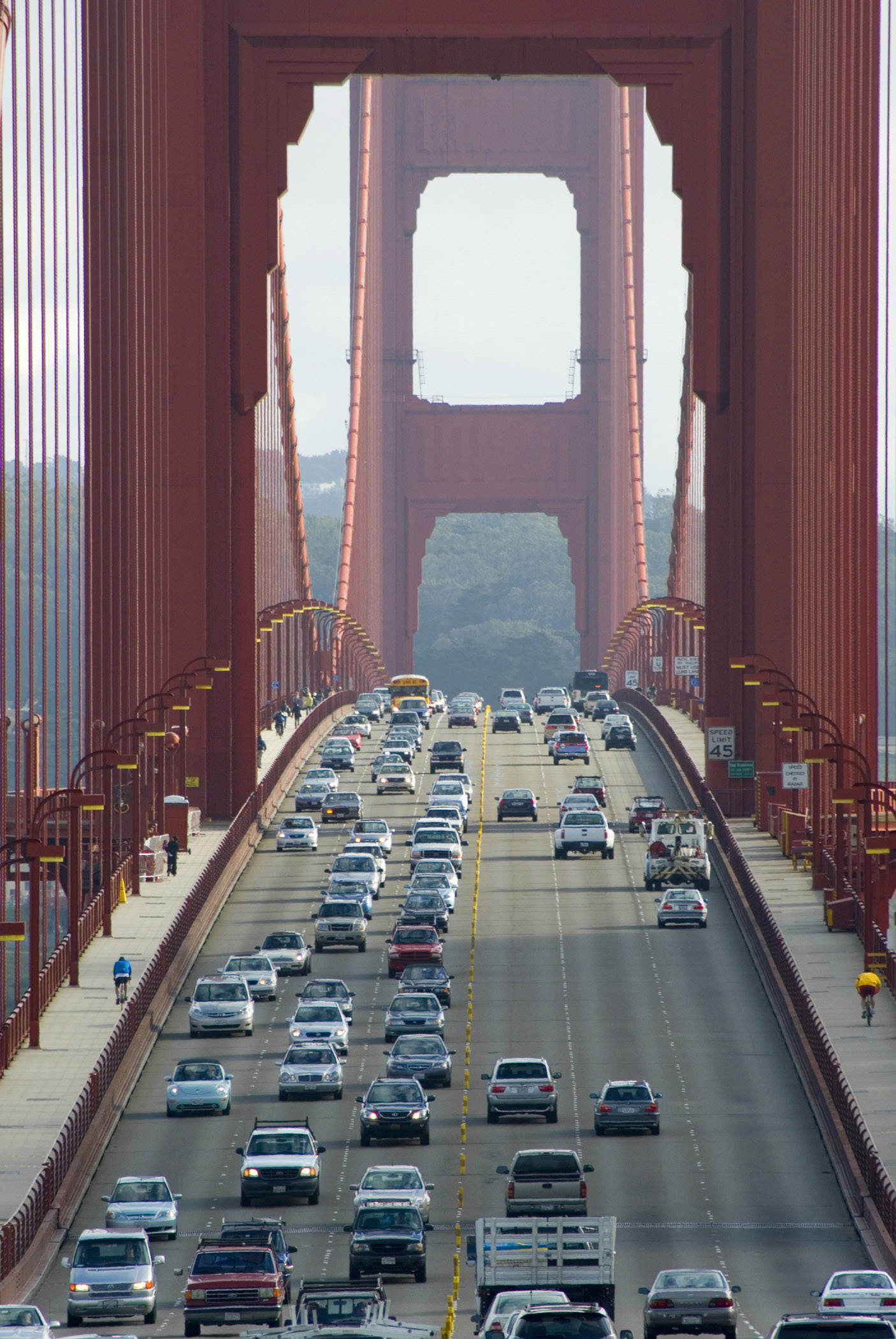 View of heavy traffic on the Golden Gate Bridge between the support towers for the suspension cables with commuters crossing the San Francisco Bay