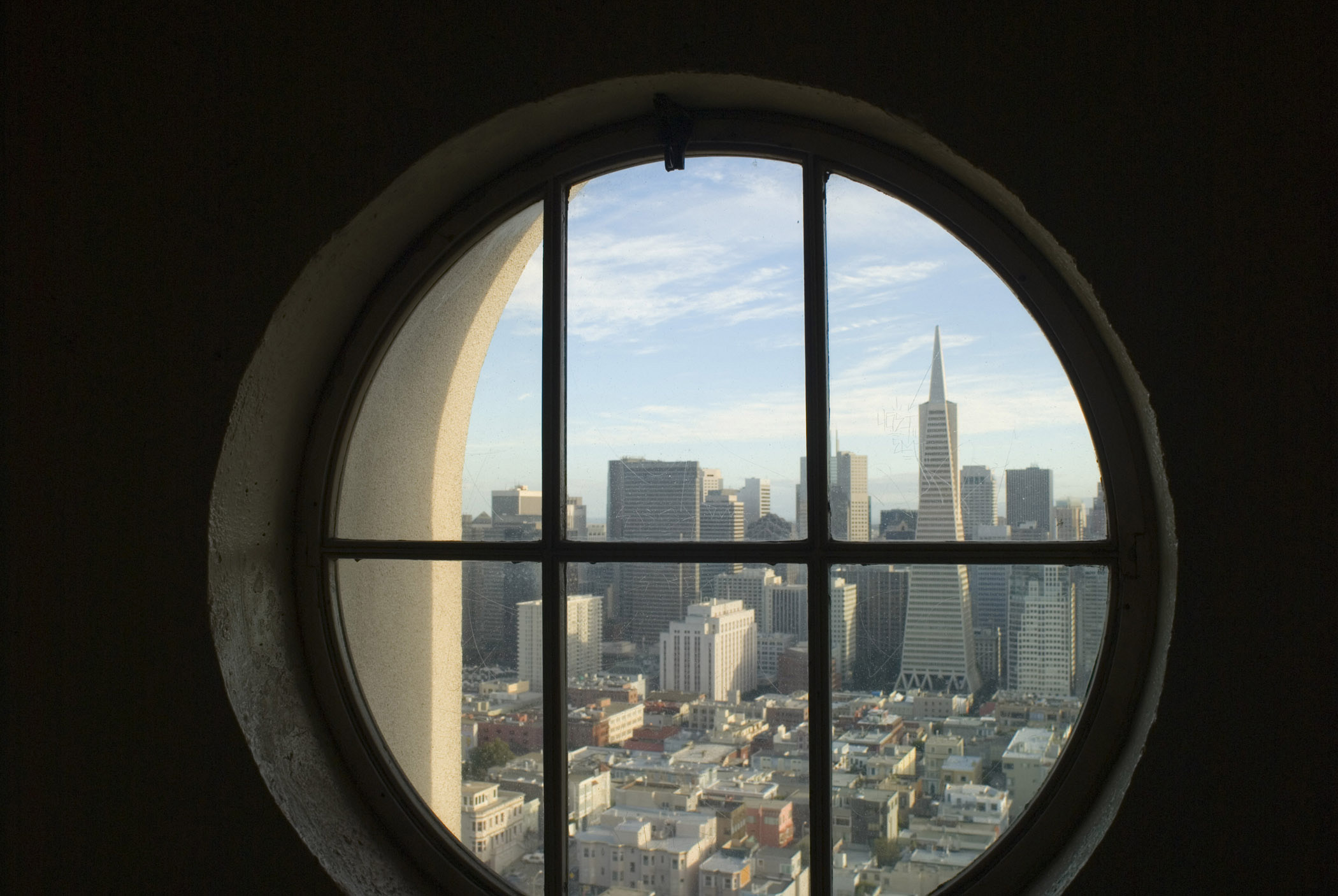 View of San Francsico from The Lilian Coit Memorial Tower looking through a round window at the CBD