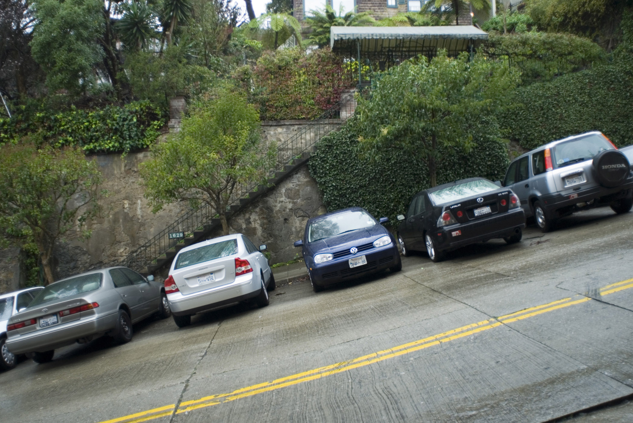 Cars parked side by side on a steep hill in San Francisco showing the steepness of the gradient on the streets leading down to the bay