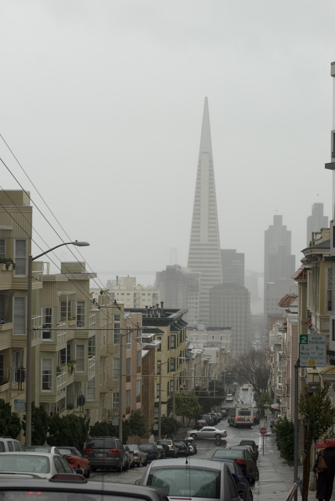 Rainy day in San Francisco, California, with a view down a steep residential hill towards the CBD and a spire through the mist