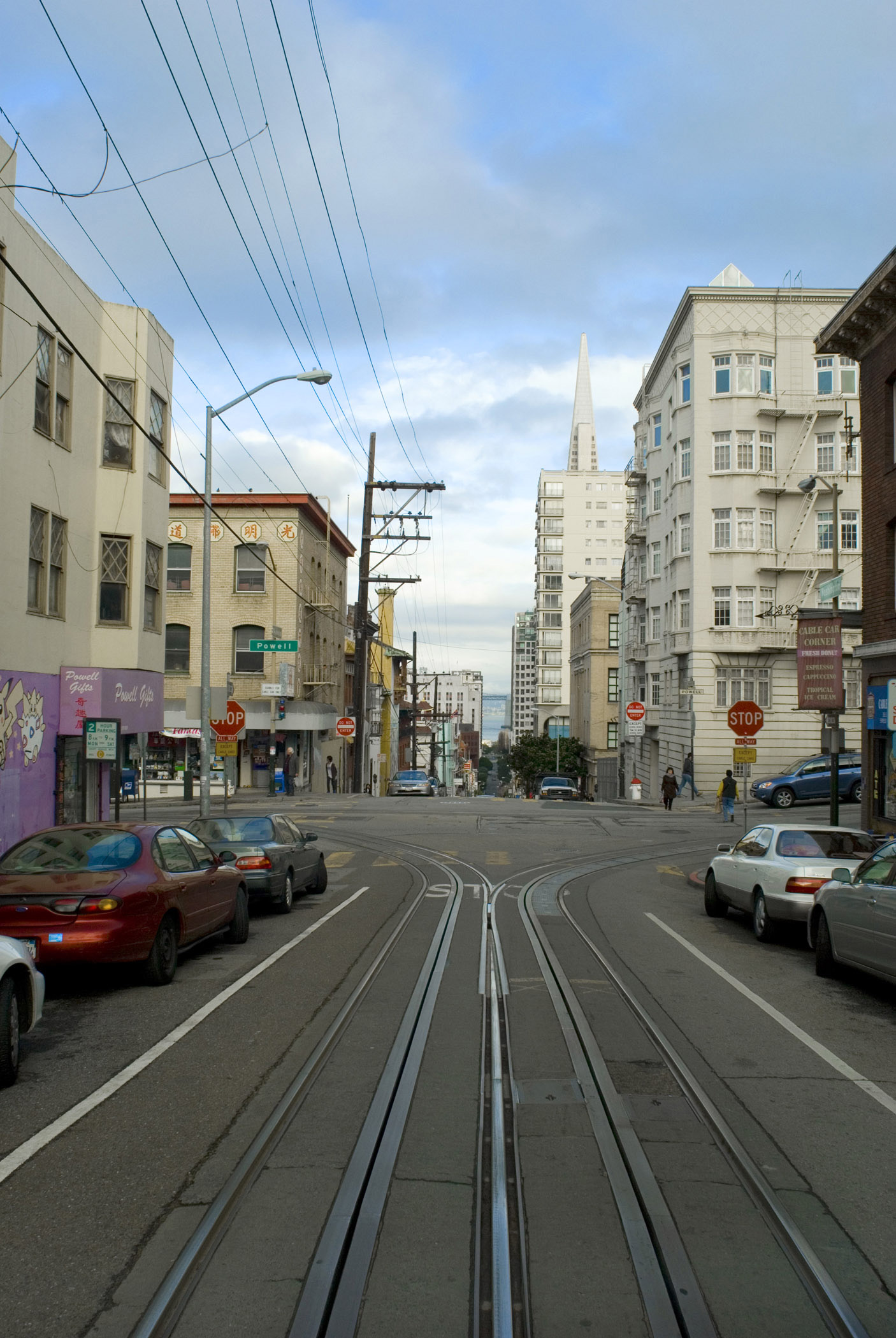 Cable car ride through the streets of San Francisco with a view out of the rear of the receding tracks and architecture of the buildings