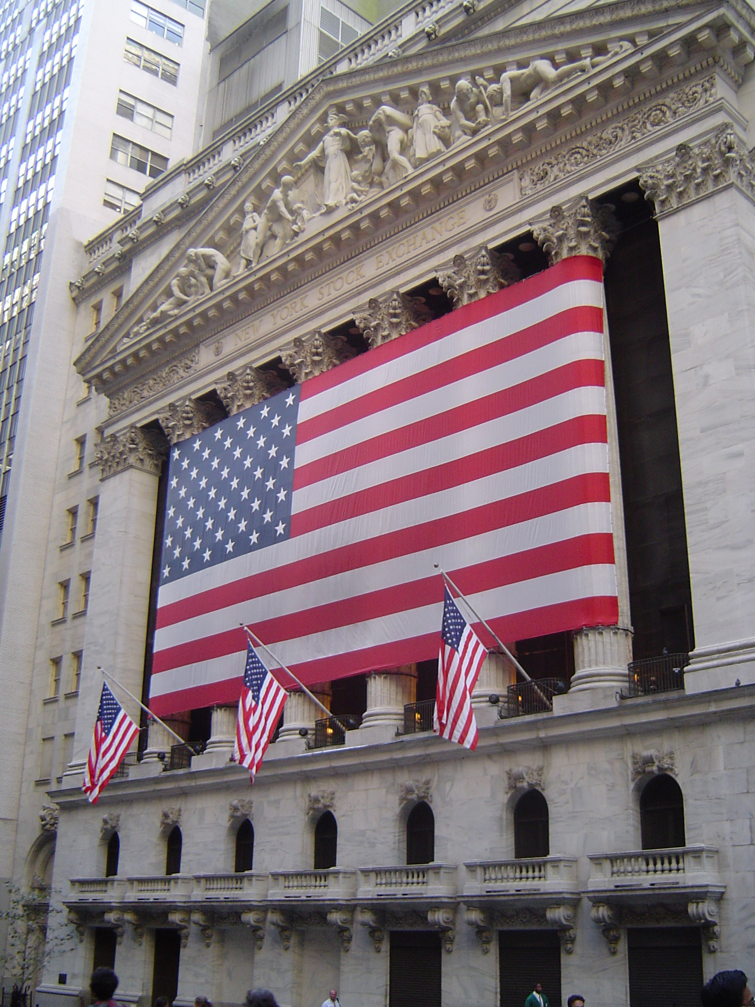 Big American Flag on Old Vintage Architectural Building at Wall Street in New York.