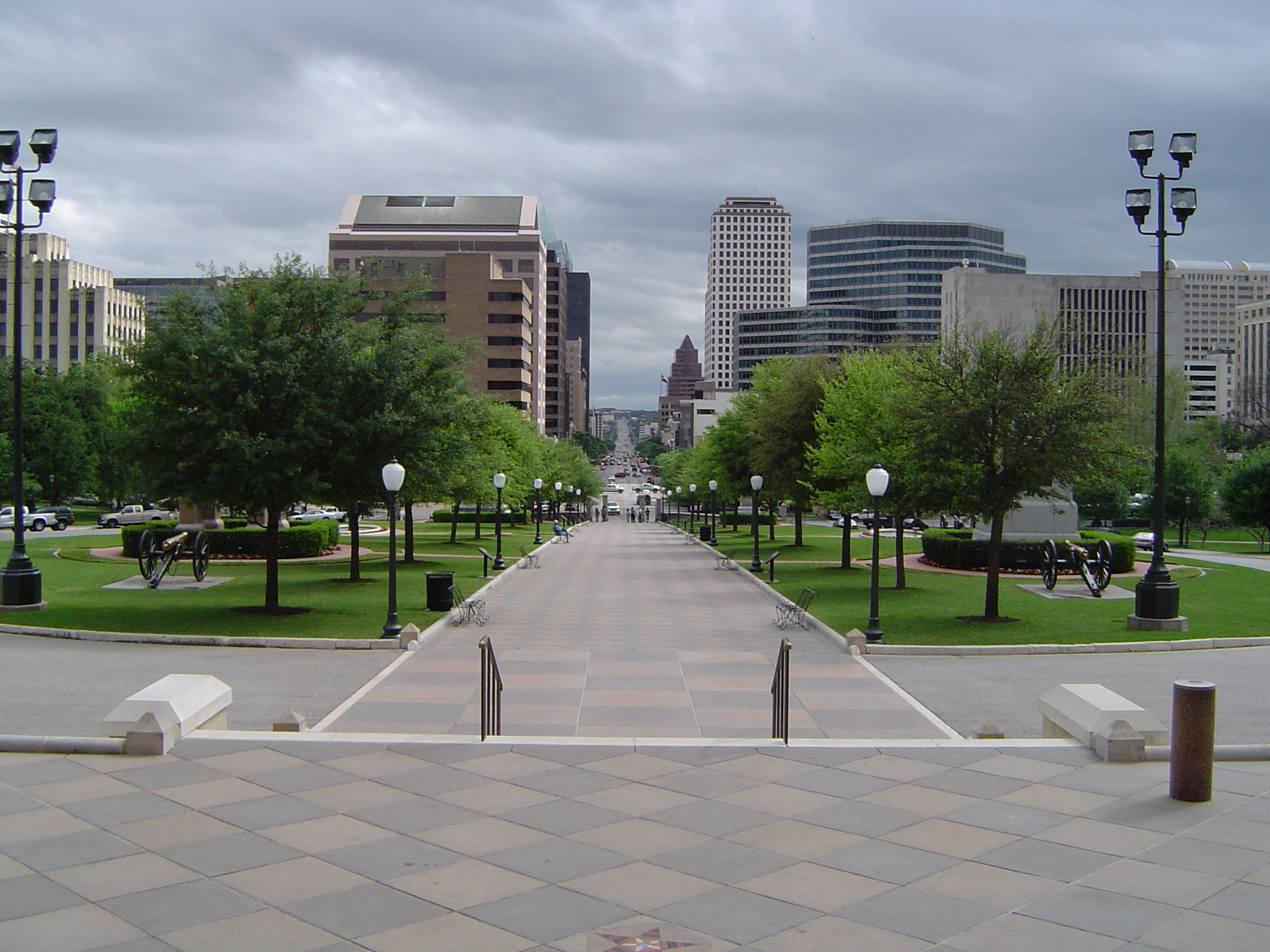 Green Trees Along Pathway at Beautiful City View of Texas with Huge Buildings Afar. Isolated on Light Gray Sky Background.