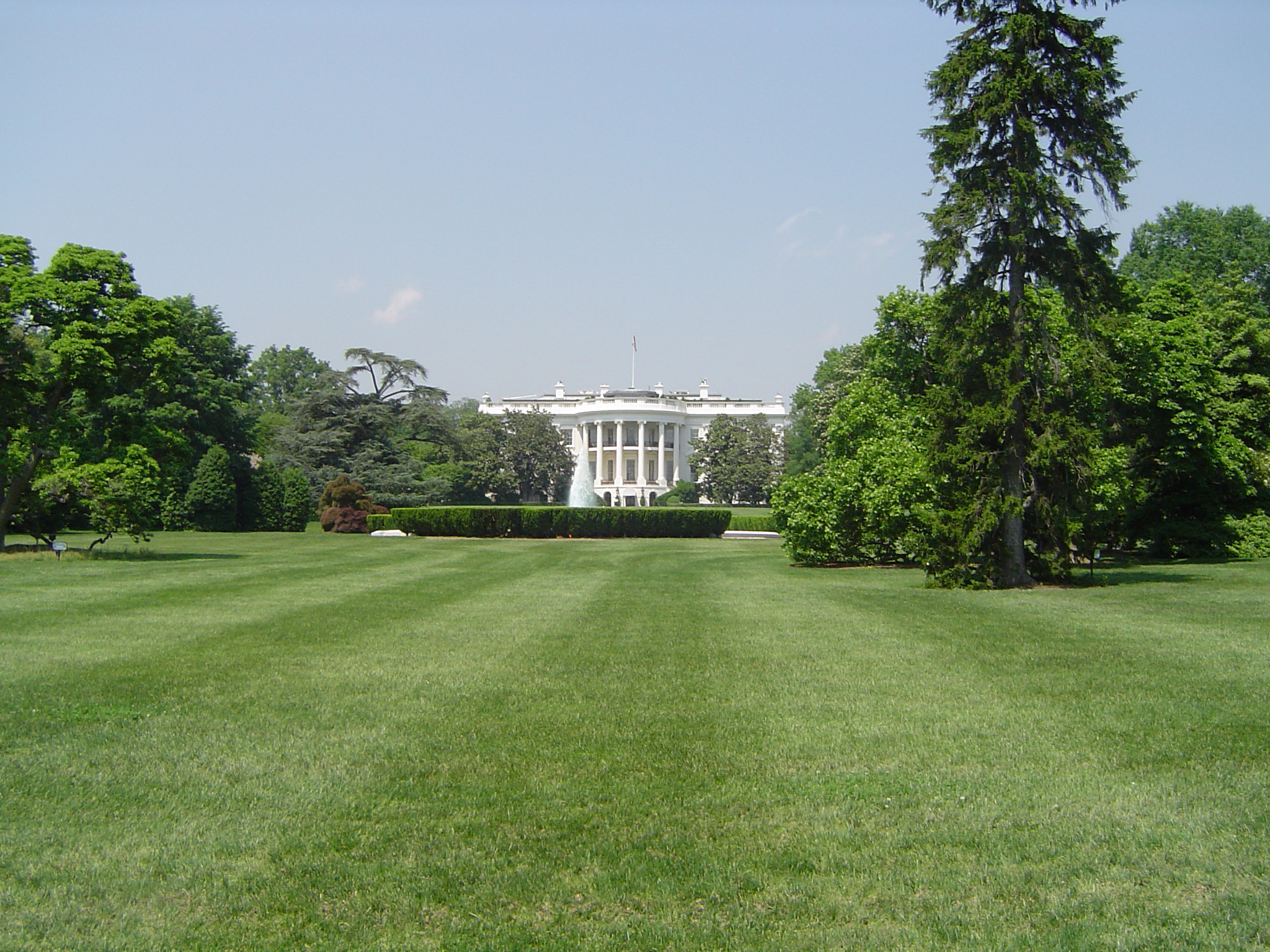 View across manicured lawns of the exterior facade of The White House, Washigton DC, USA