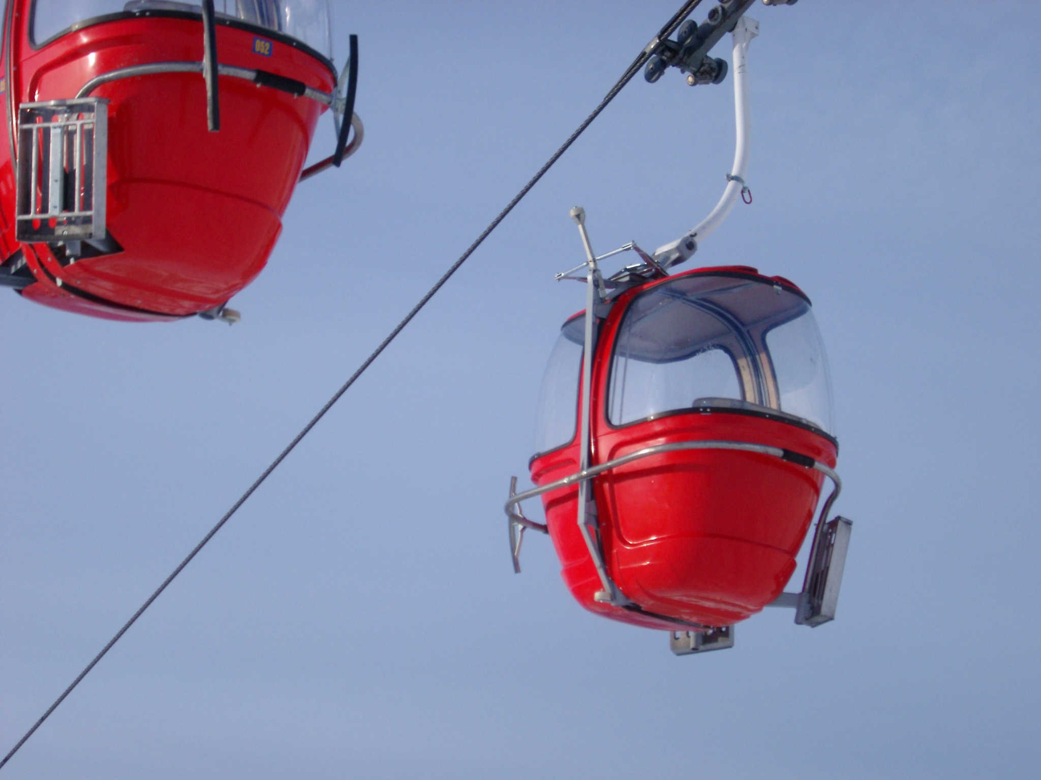 High-Tech Empty Red Cable Cars for Adventure on Lighter Blue Sky Background.