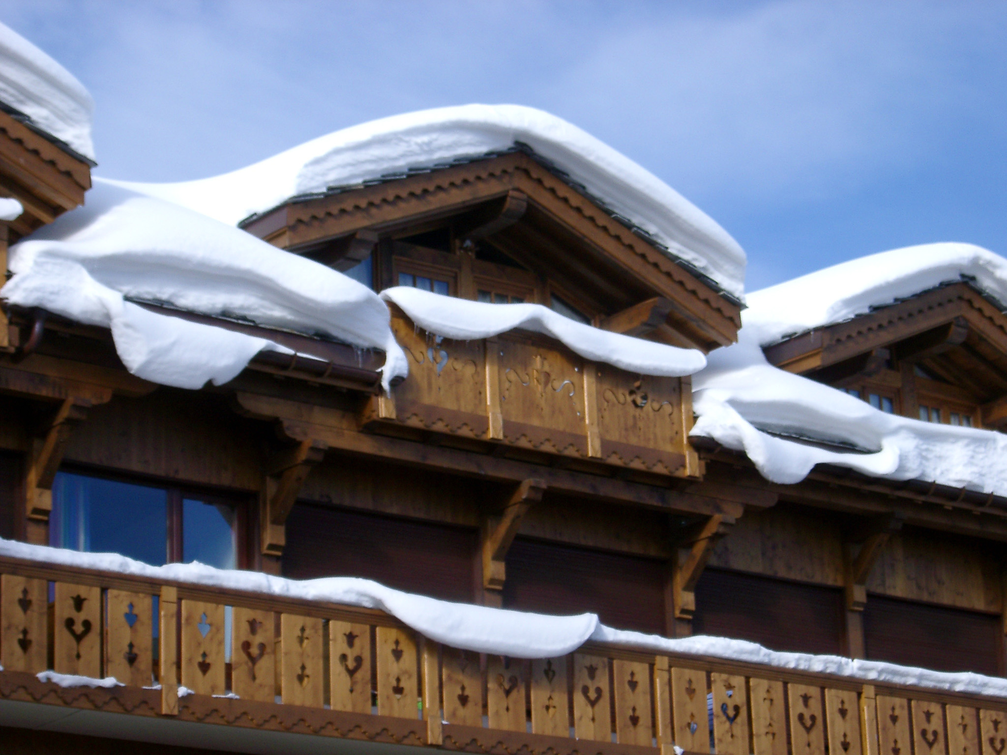 Detail of the roof and balconies of a traditional wooden alpine lodge covered in snow against a sunny blue sky