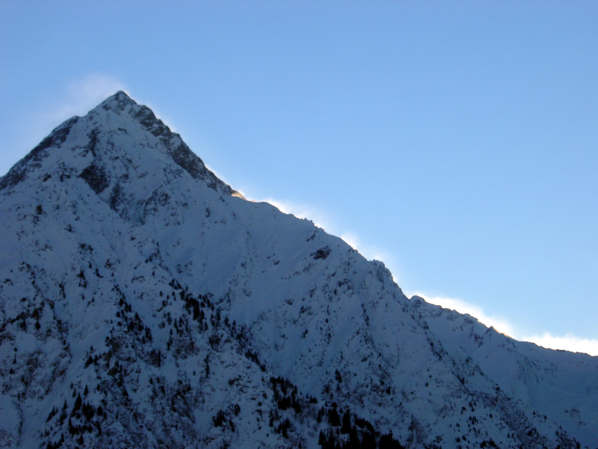 Sunrise of a snow covered mountain peak gilding the rim with a golden glow against a clear blue winter sky