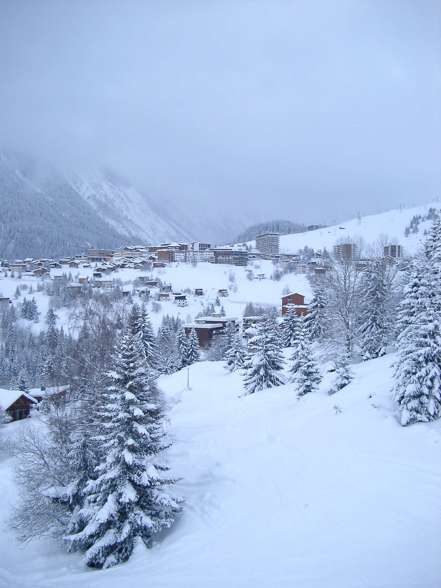 Scenic winter landscape with snow covered fir trees and an alpine village in a high mountain valley