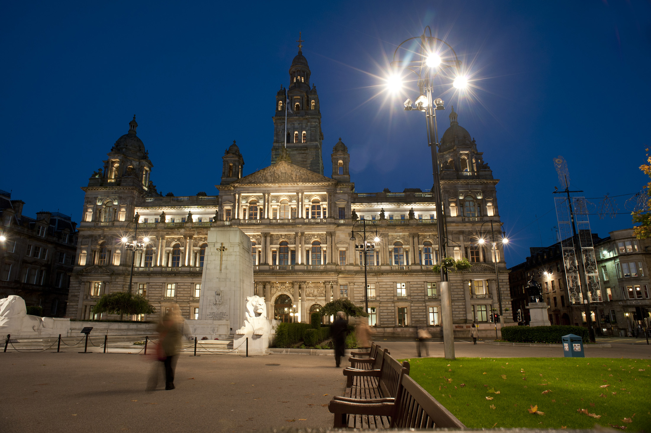George Square, Glasgow at night looking towards the historical external facade of the Glasgow City Council building with pedestrians crossing the square