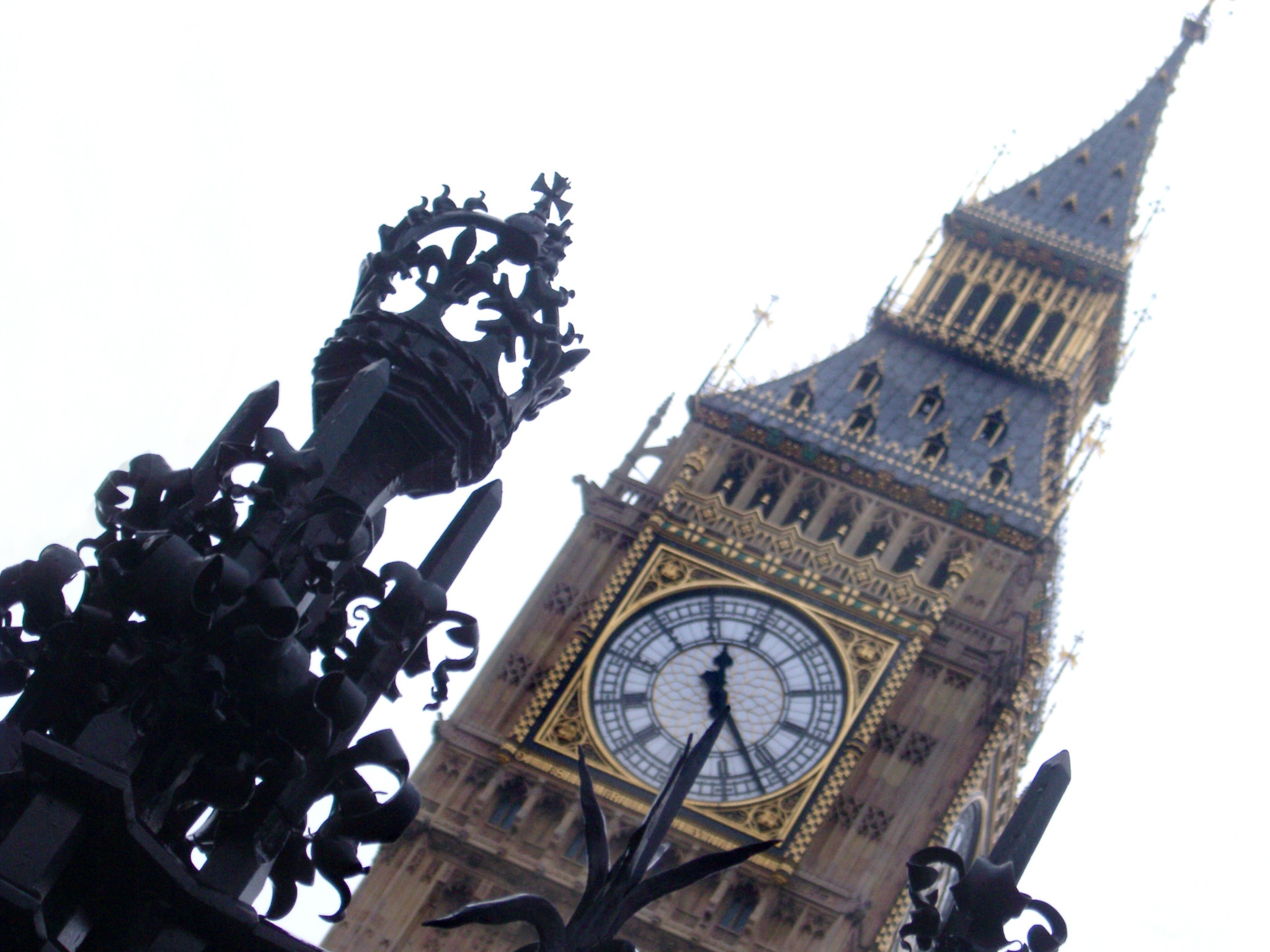 Tilted angle view of ornate wrought iron work and the clock face of Big Ben, the clock tower for the old palace of Westminster, now an iconic landmark and tourist attraction