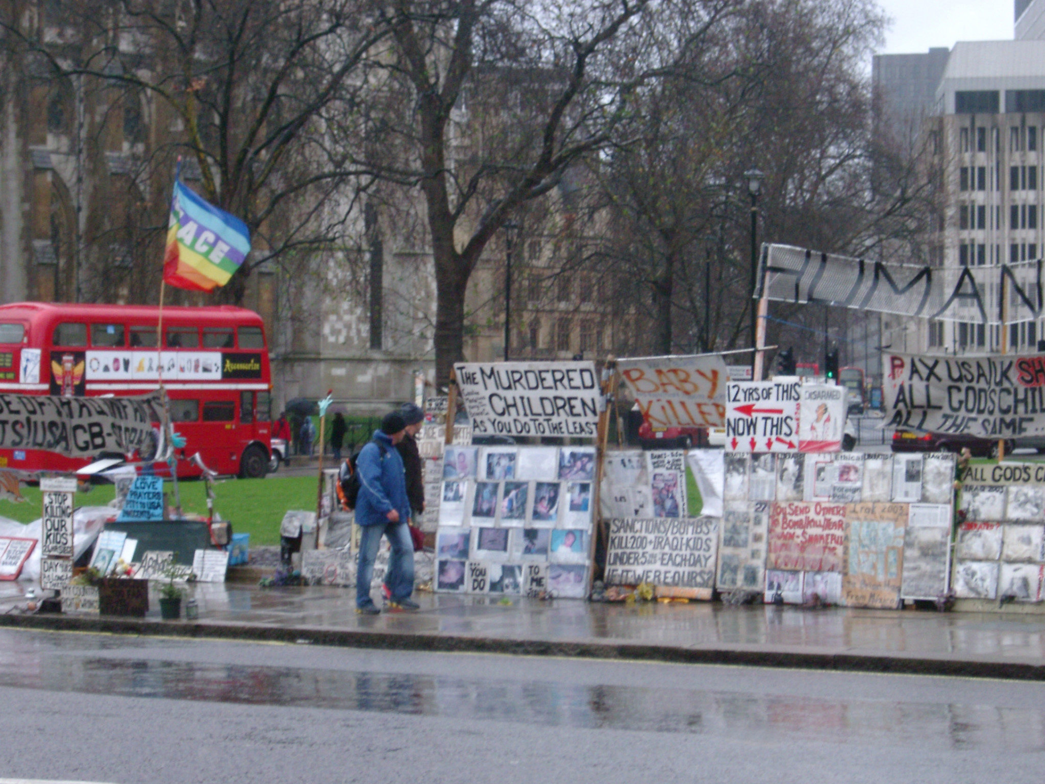 Streetside demonstartion in London with a pedestrian walking past a display of placards and slogans on a wet rainy day