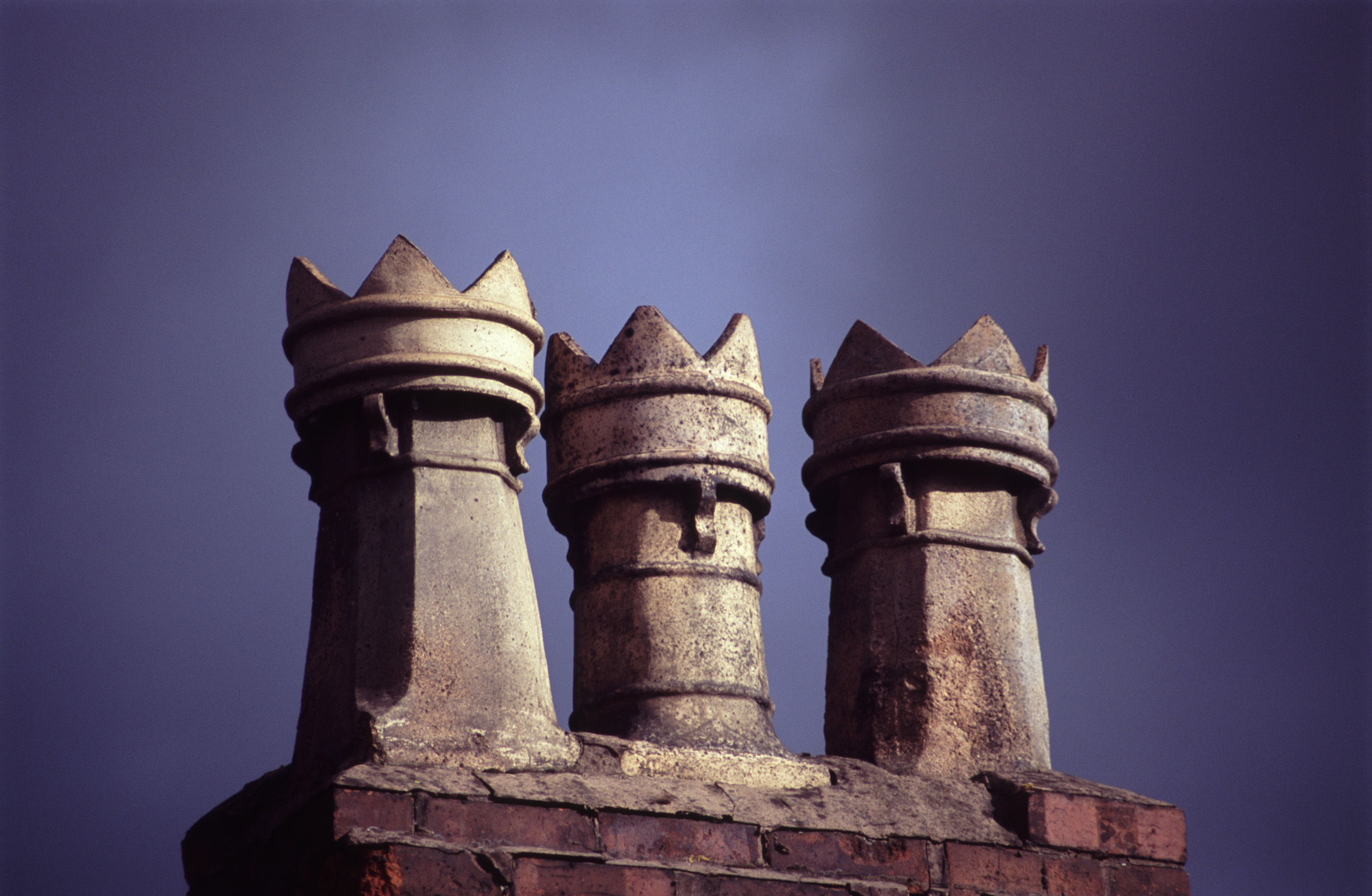 Row of chimney pots in Stockport on a rooftop, close up against a dark threatening stormy sky