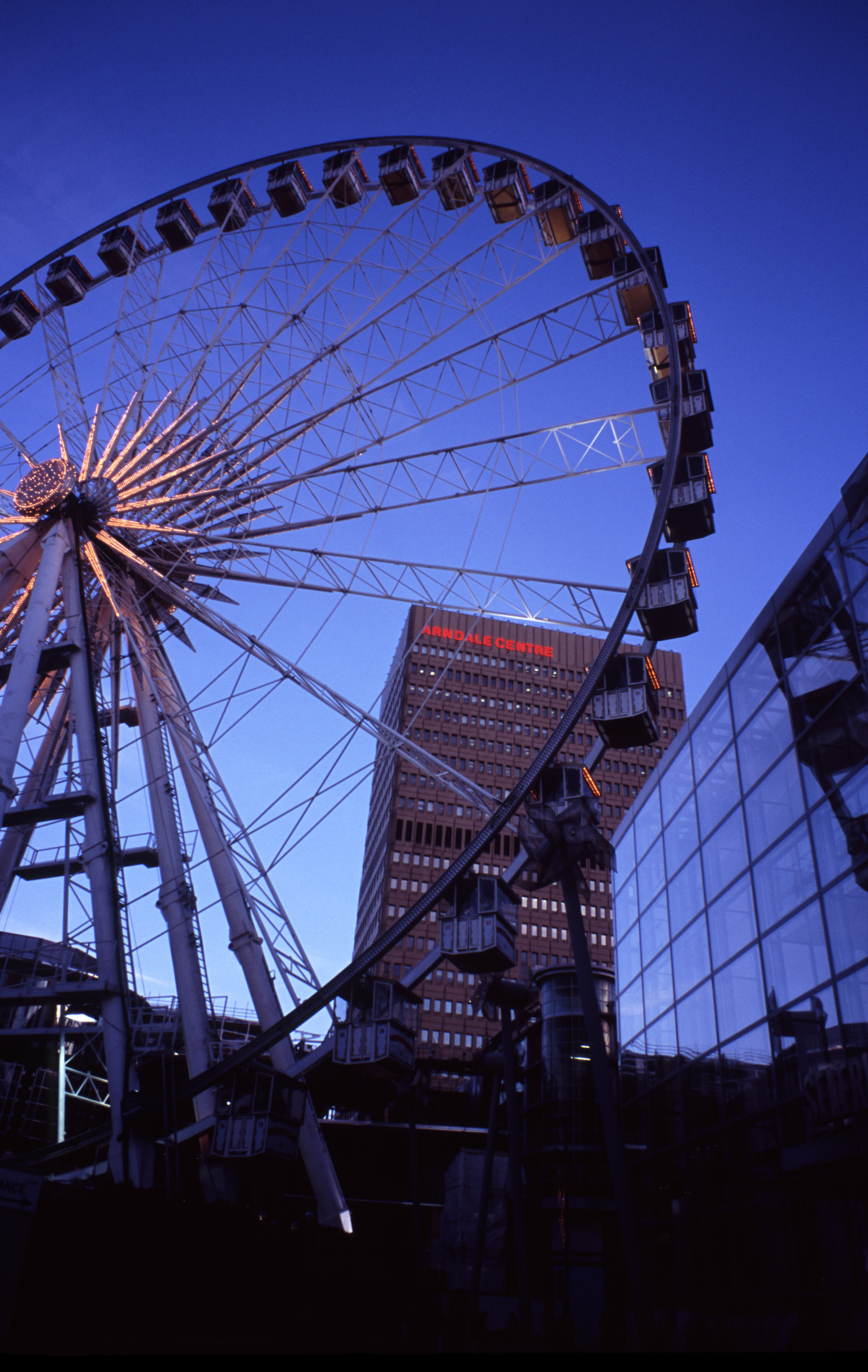 The Manchester Wheel - Famous Transportable Ferris wheel Installation at Piccadilly Gardens, Manchester, England. Captured at Night Time.