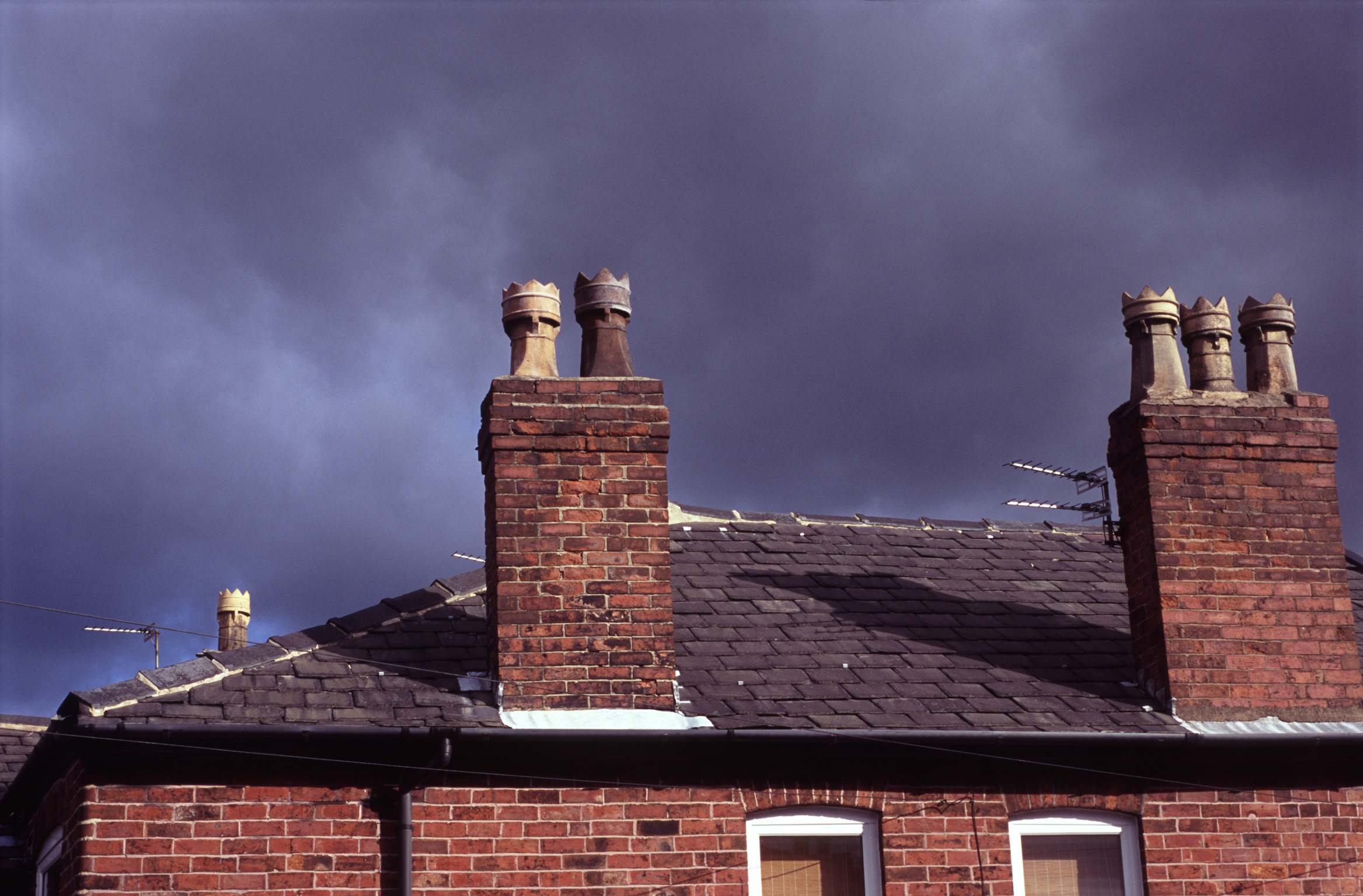 Red brick chimney pots on old terraced houses in Stockport against an ominous cloudy sky