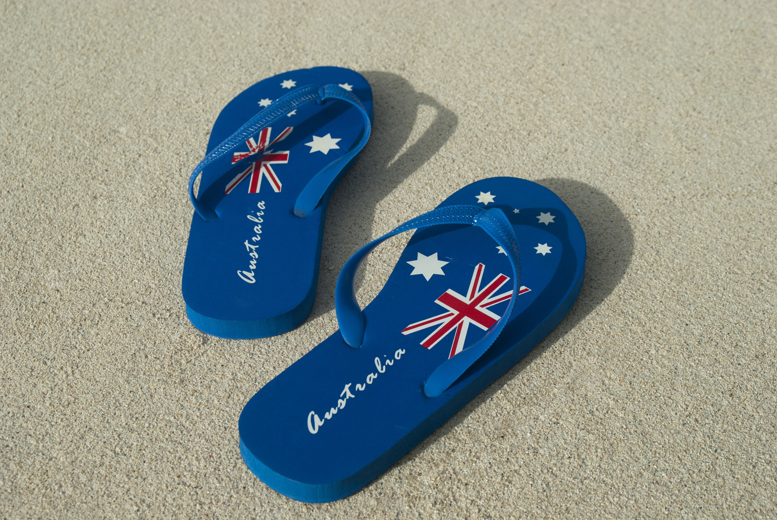 A pair of blue Australia day thongs with national flag design on a sandy beach.