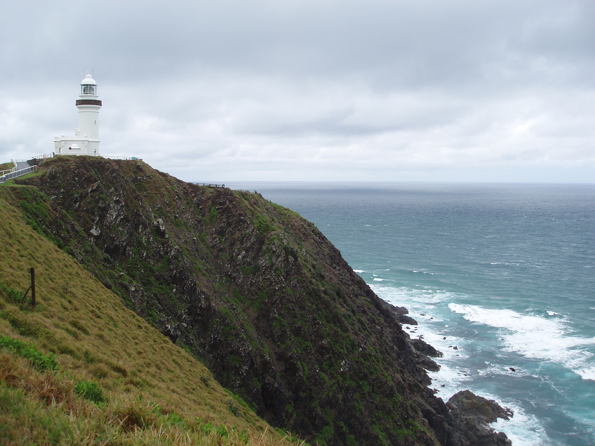 Lighthouse at Grassy High Cliff at Beautiful Byron Bay in Australia on Light Gray Sky Above.