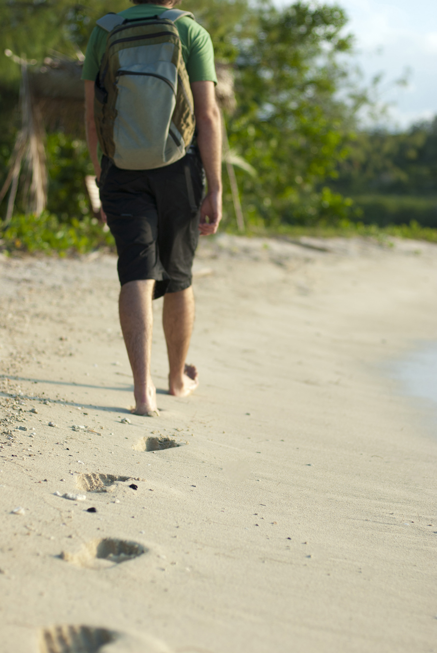 Man wearing a backpack walking away along a sandy beach leaving a trail of footprints