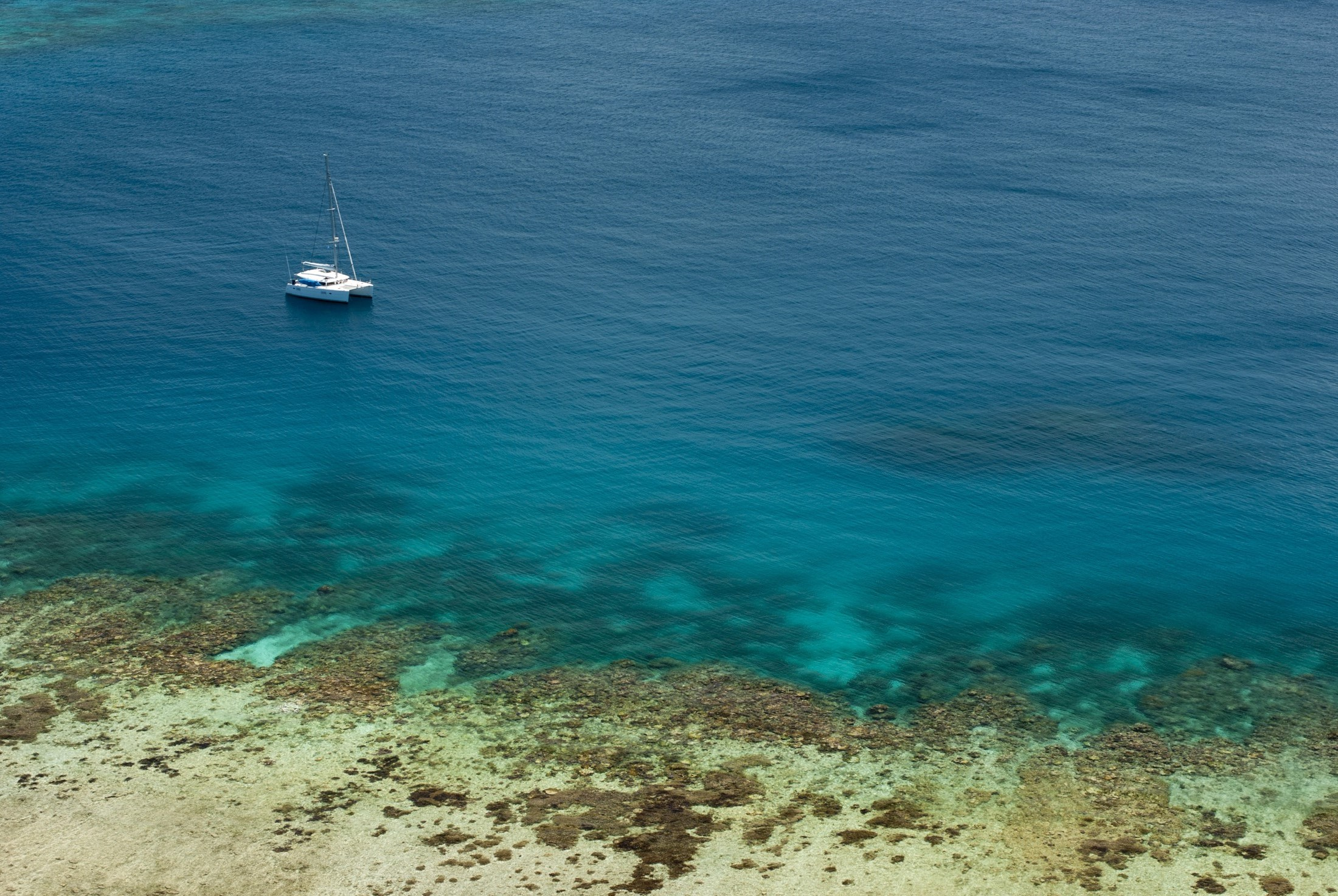 Blue ocean and crystal clear shallows off Yasawas Island, Fiji with a yacht passing close to shore and copyspace